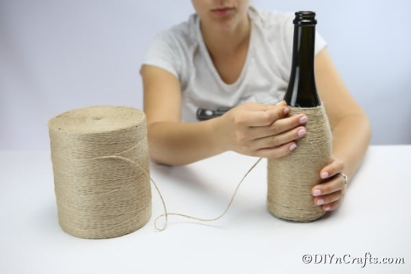 Wrapping a wine bottle with twine to create a nautical decor piece