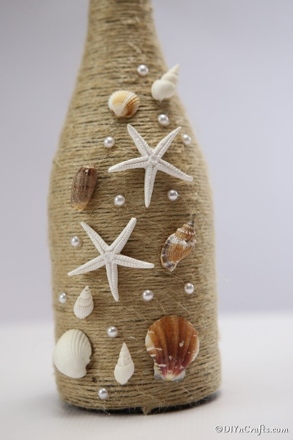 Up close picture of the shells attached to a nautical wine bottle decor piece