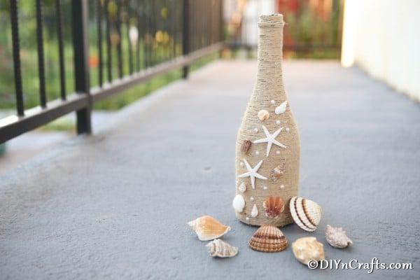 Rustic wine bottle decor displayed with shells ona concrete walkway