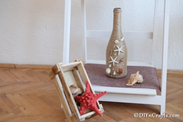 A nautical twine wrapped bottle displayed on a small shelf next to other seashells