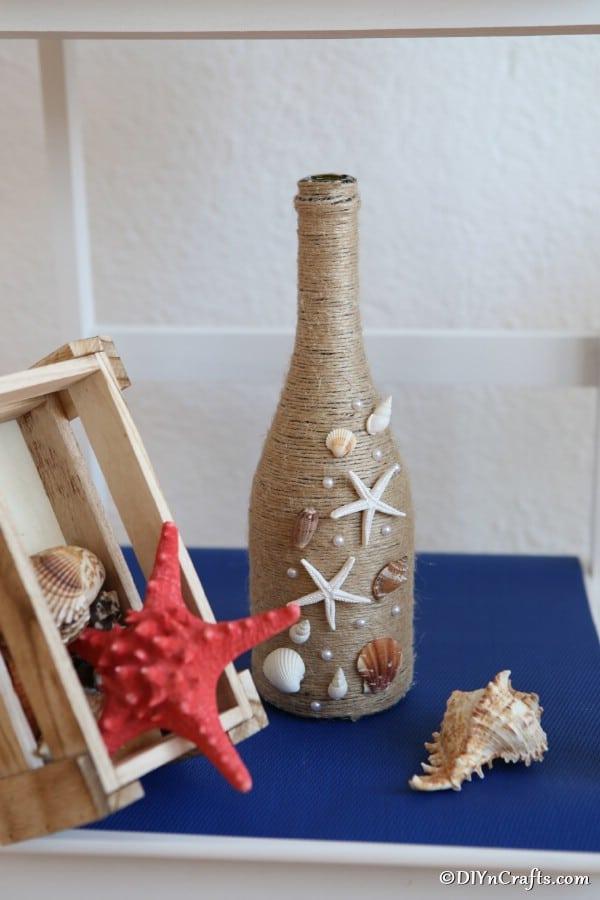Nautical wine bottle decor on a blue shelf with other seashells