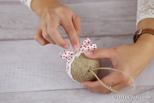 Adding a ribbon bow to the front of the rustic ornament