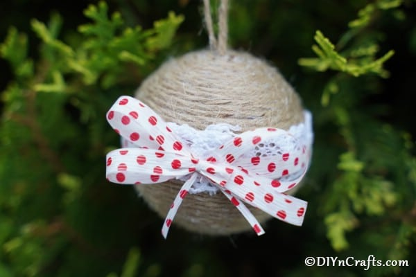 Up close picture of a ribbon & lace rustic Christmas ornament hanging on a tree