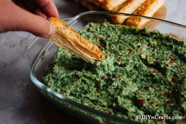 Hot spinach dip in a large clear bowl with breadstick dipping into it