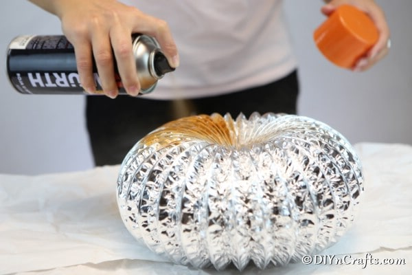 Spray painting the dryer vent with orange paint for pumpkin decor