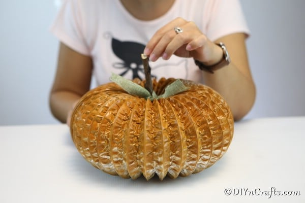 Adding twig and leaf to the dryer vent pumpkin decor craft
