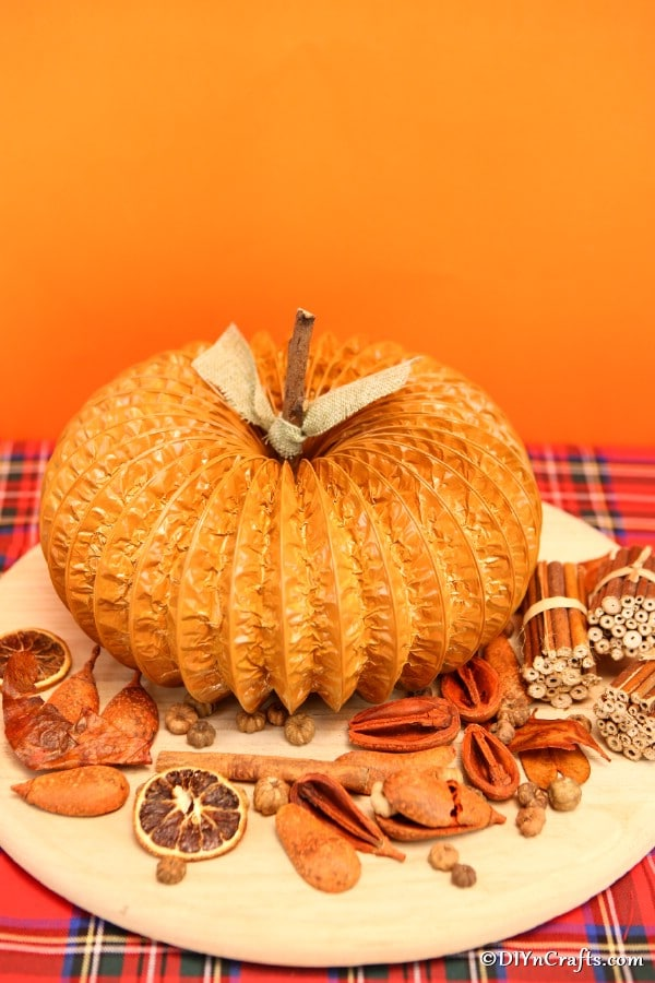 Pumpkin decor sitting on a table with other fall items in front of an orange background