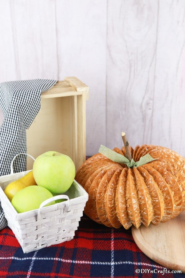 A dryer vent pipe pumpkin decor piece sitting on a plaid fabric on a table with a basket in background