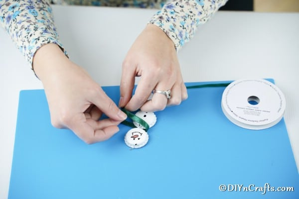 Tying a ribbon onto the bottle cap snowman ornaments