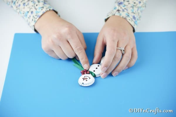 Adding Christmas berries to snowman scarf