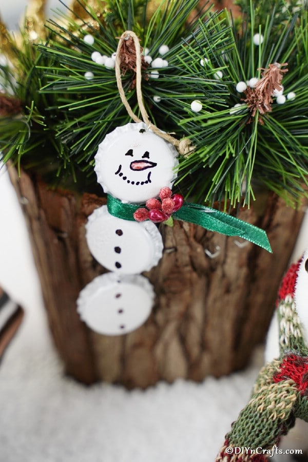 Bottle cap snowman ornament hanging on a wooden stump with greenery
