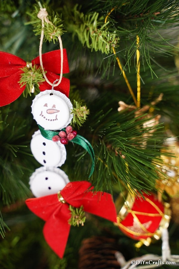 A bottle cap snowman ornament hanging on a Christmas tree