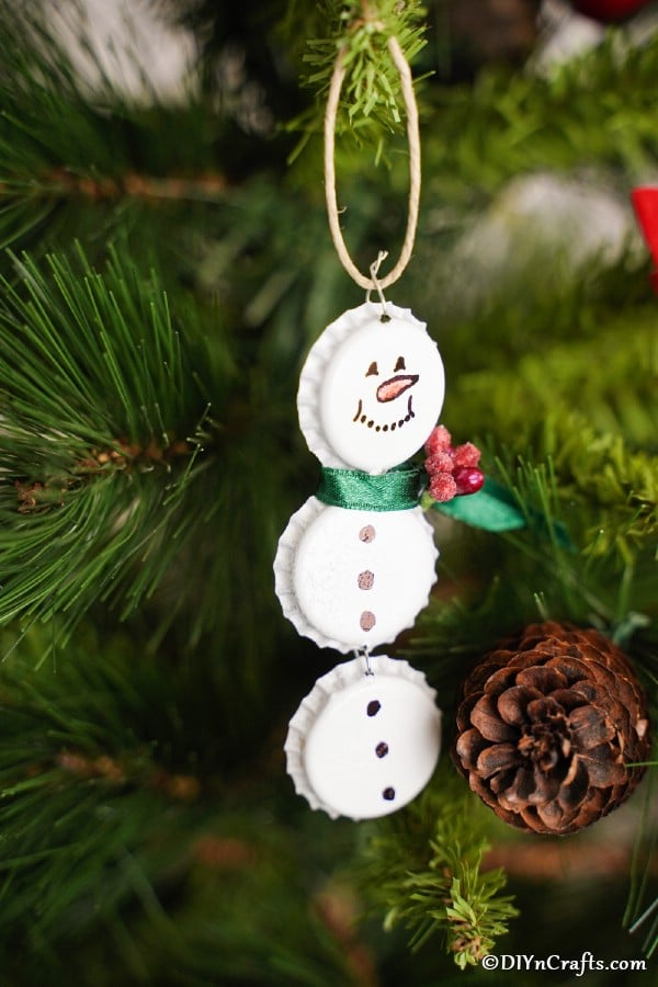 Up close picture of bottle cap snowman ornaments on a tree