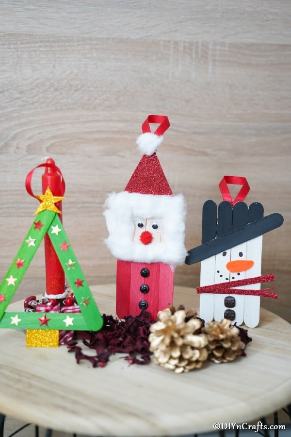 A trio of craft stick ornaments displayed on a table