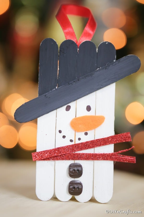 A snowman craft stick ornament displayed on a table in front of the holiday tree