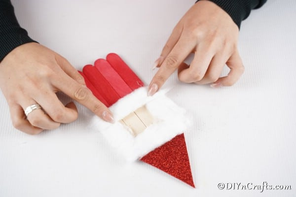 Adding cotton to create a face on your Santa ornament