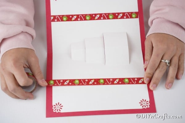 Attaching the card to the red cardstock with glue