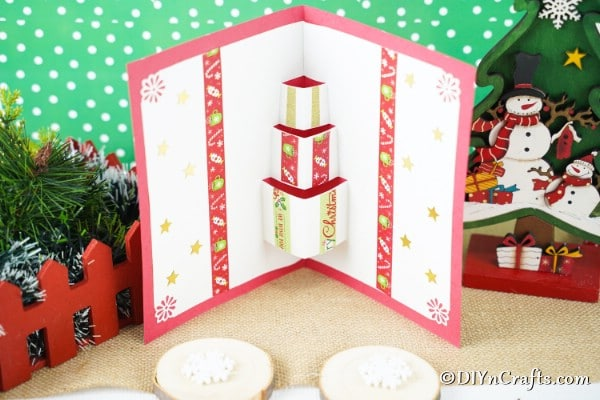 A gift box 3D Christmas cards craft displayed with holiday decor in front of a green and white background