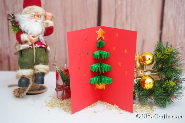 A 3d Christmas tree card sitting displayed on a wooden surface with a santa in the background