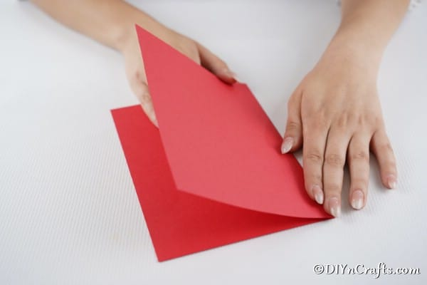 Folding red paper in half to create a 3d card for Christmas