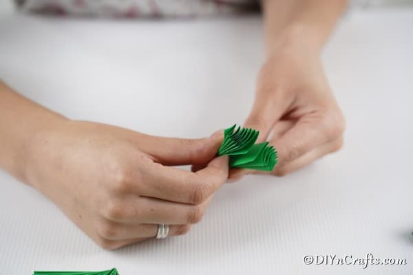 Folding green fan pieces into holiday tree trunks for the 3d Christmas tree card