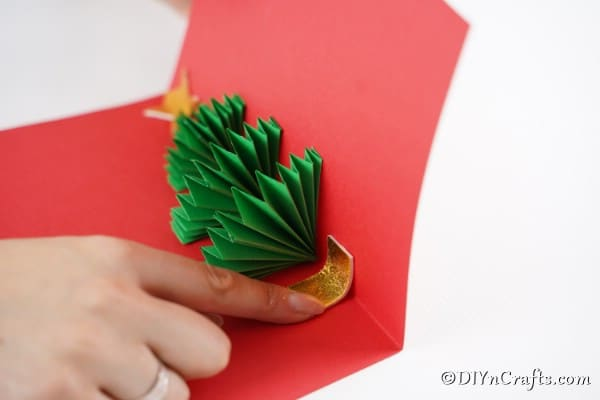 Gluing a gold star at the top of a 3D Christmas tree card