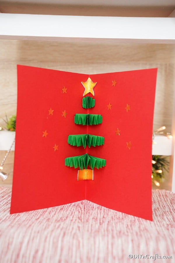 A red and green 3-d Christmas tree card on display