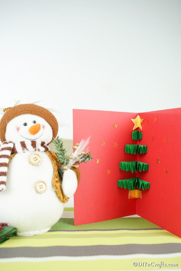 A 3D Christmas tree card displayed next to a snowman figurine