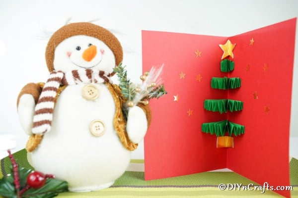 A red and green 3D Christmas tree card sitting next to a toy snowman