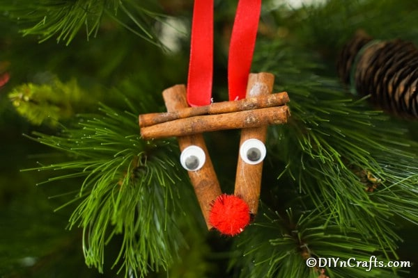 A cinnamon stick reindeer ornament hanging in a Christmas tree