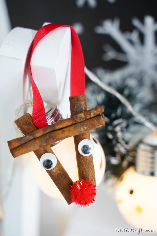 Cinnamon stick reindeer ornament hanging on a mantle