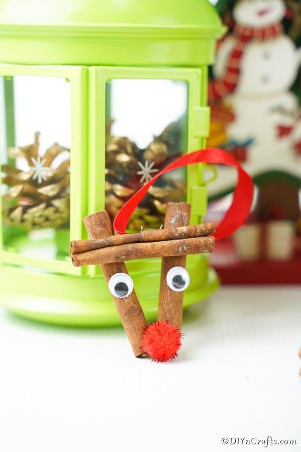 A cinnamon stick reindeer ornament leaning against a green lantern