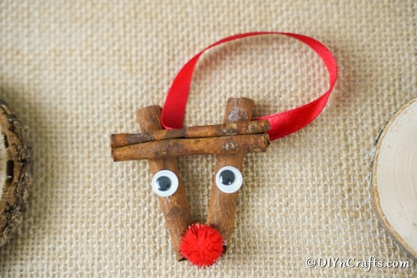 A cinnamon stick reindeer ornament laying on a brown cloth
