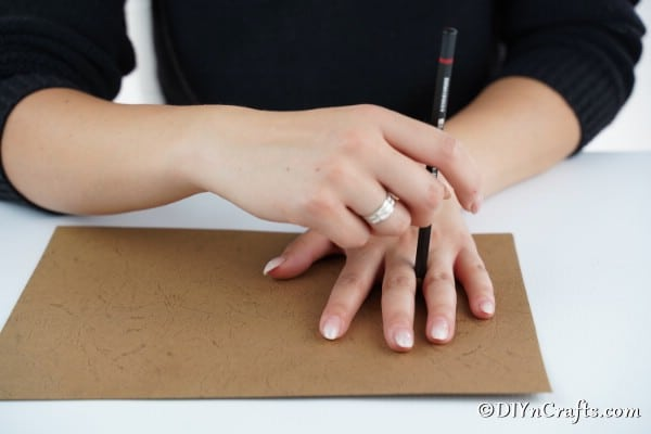 Tracing hands on a piece of cardboard to attach to a flower pot reindeer craft