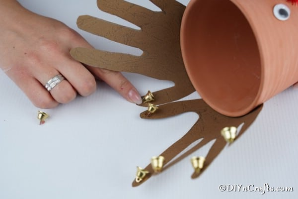 Gluing jingle bells onto the horns of a reindeer flower pot decoration