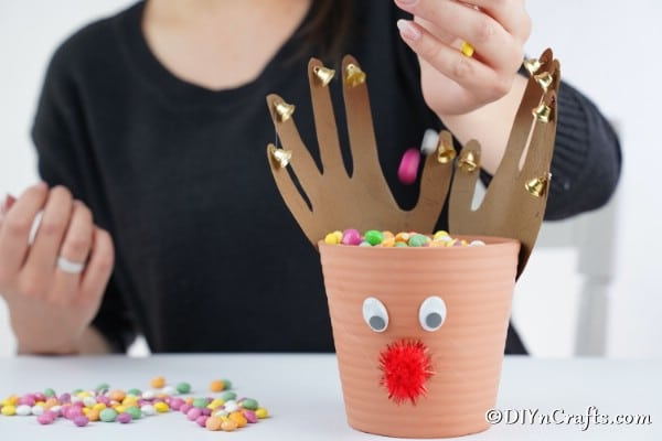 Filling a reindeer flower pot with candy