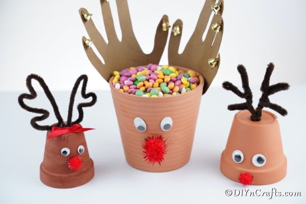 A trio of reindeer flower pot decorations sitting on a white surface