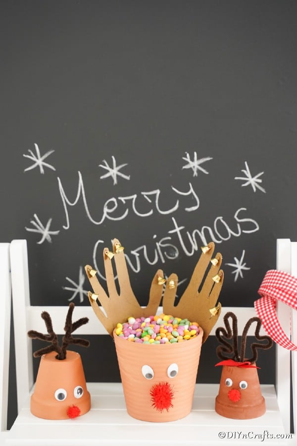 Flower pot reindeers sitting on a white shelf in front of a Christmas chalkboard