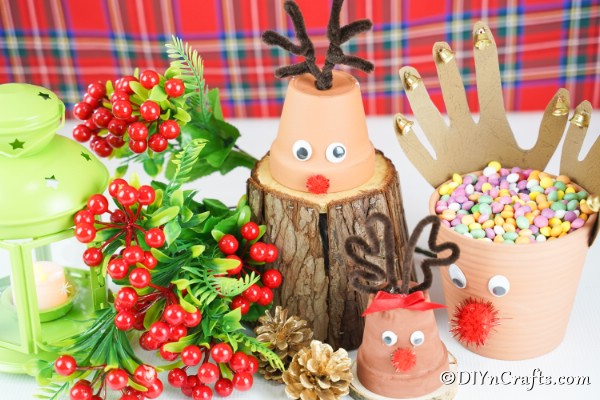 A display of reindeer Christmas decor on a table with other holiday decor