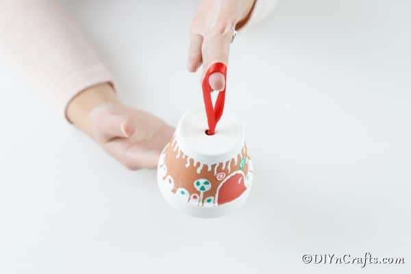 Adding a ribbon to the top of the flower pot gingerbread house