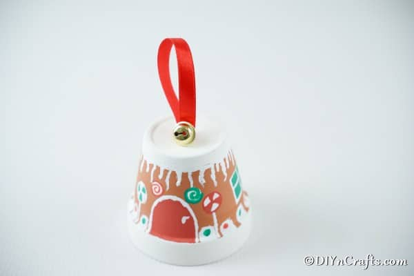 Adding the jingle bell to the top of the gingerbread flower pot craft