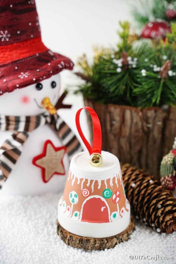 A gingerberad house clay pot on a shelf with holiday decorations in the background