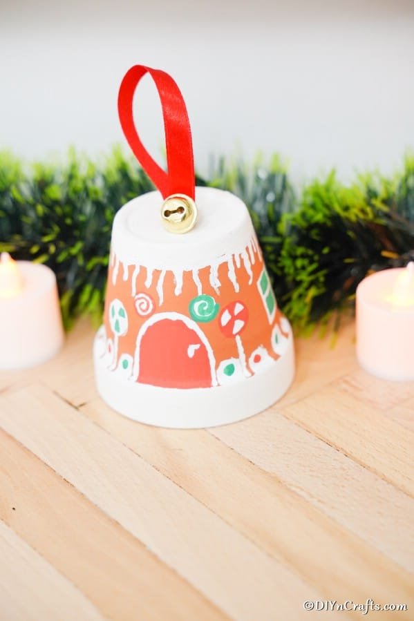 A gingerbread house flower pot on a wooden table with greenery