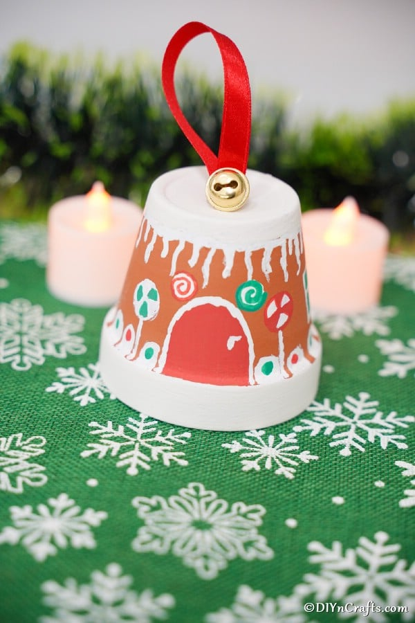 A gingerbread house flower pot winter craft on a green and white snowflake surface