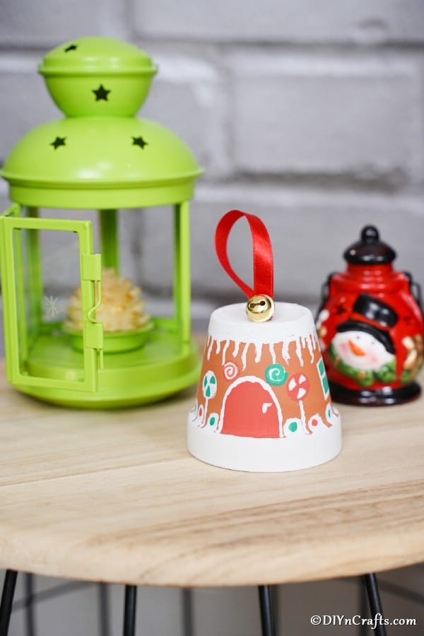 A gingerbread house clay pot sitting on a wooden table with green lantern in the background