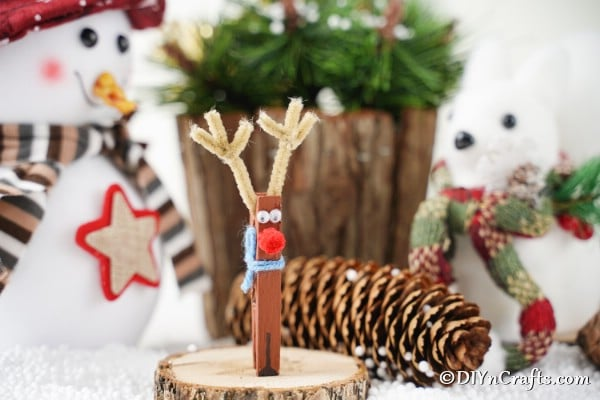 Cute clothespin reindeer ornament sitting on a slice of wood next to holiday decorations