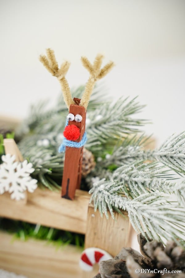 Reindeer clothespin ornaments on display next to holiday greenery