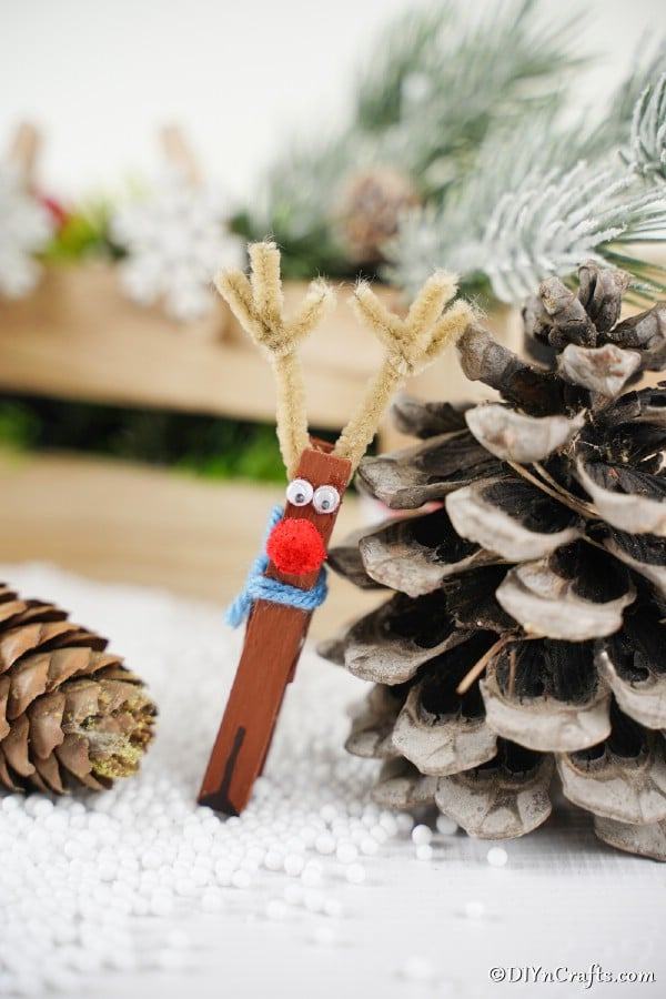 A clothespin reindeer leaning against a pinecone