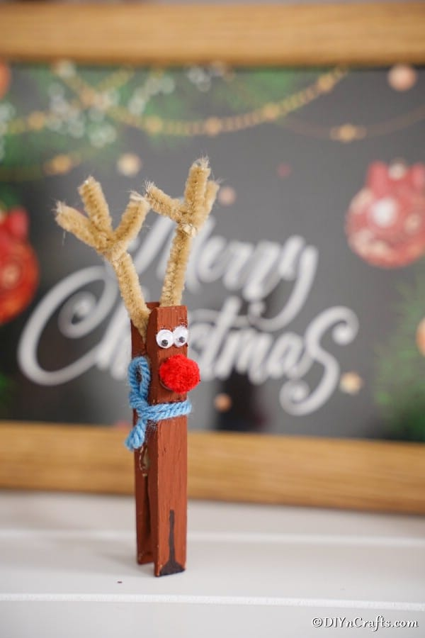 A clothespin reindeer sitting in front of a merry christmas sign