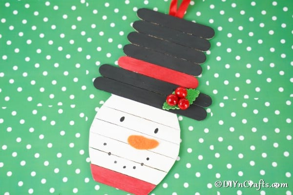 Popsicle stick snowman craft laying on green polka dot surface
